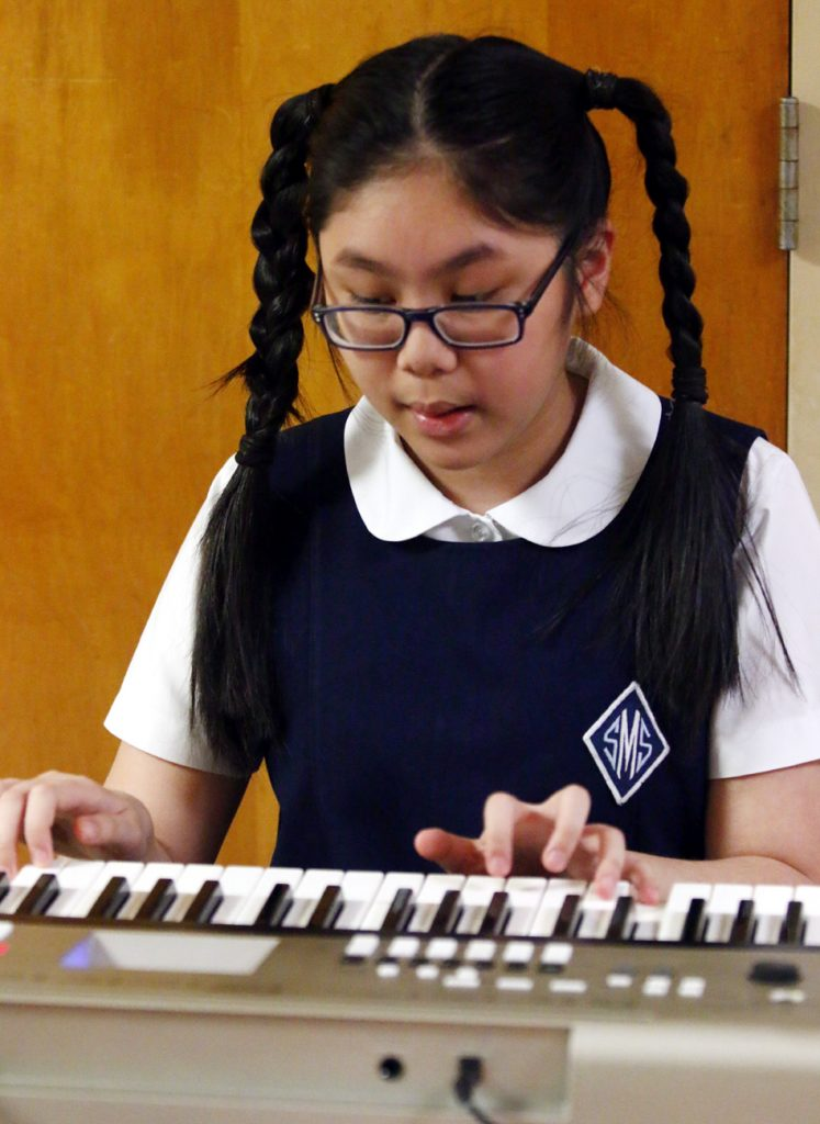 St. Monica School's Vy Trinh-Nguyen, in sixth grade, fills the hall with music at the March 28 Showcase of Excellence at SS. Neumann and Goretti High School in South Philadelphia.