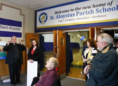 Father Joseph Maloney (left), pastor of St. Aloysius Parish in Pottstown, offers remarks at the formal handover of the keys to the new school building. (Sarah Webb)