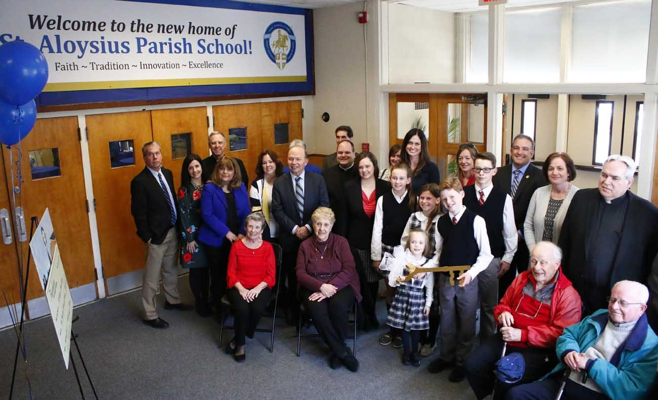 The St. Aloysius School community along with representatives of the Foundation for Catholic  Education and parish faithful and leadership, formally received the keys and ownership of the former St. Pius X High School -- the new home of St. Aloysius School -- on March 24. (Sarah Webb)