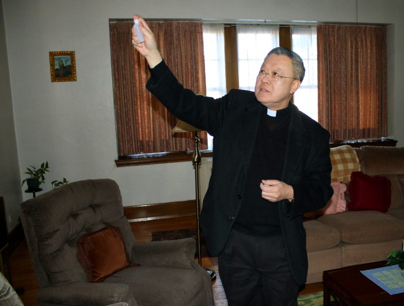 Msgr. Joseph Trinh, pastor of St. Helena Parish, blesses the Outreach Center.