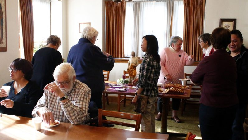 After the blessing of the new outreach center at St. Helena Parish in Philadelphia by the pastor, Msgr. Joseph Trinh, committee members and volunteers for the Outreach Center gather for refreshments. (Sarah Webb)