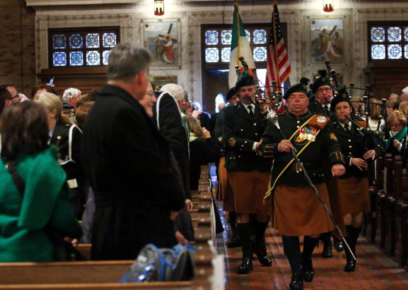 The Philadelphia Emerald Society Pipe Band leads the grand marshal into church before Mass.
