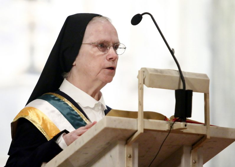Sister James Anne Frank, I.H.M., parade chaplain, reads from Scripture during the Mass observing St. Patrick's Day.