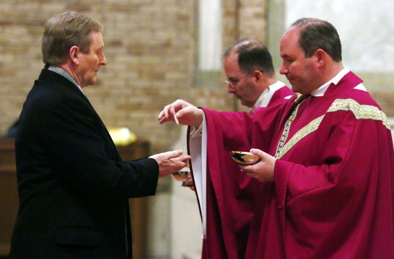 Father Kevin Gallagher, chaplin, distributes holy communion to Irish Prime Minister Enda Kenny.