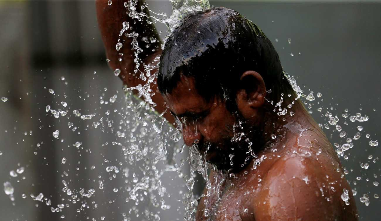 A man bathes at a public well in Colombo, Sri Lanka, March 22. (CNS photo/Dinuka Liyanawatte, Reuters)