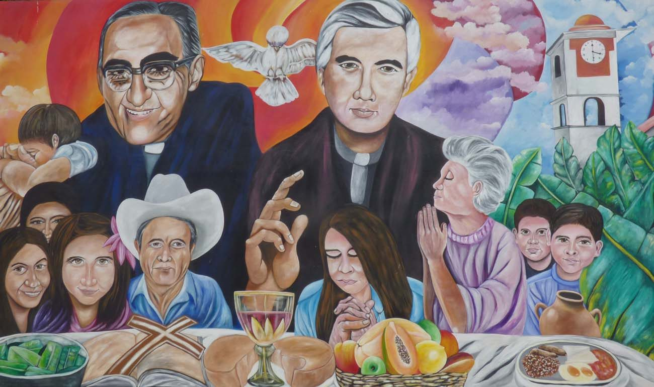 A mural in El Paisnal, El Salvador, seen in this Jan. 29 photo, features Blessed Oscar Romero and town native Father Rutilio Grande, surrounded by rural men, women and children, the community the Jesuit Father Grande served from 1972 until his March 12, 1977, assassination. Father Grande spoke of his dream of a communal table where everyone, including the poor, had a place to eat and a right to have a say in matters that affected them. (CNS photo/Rhina Guidos)