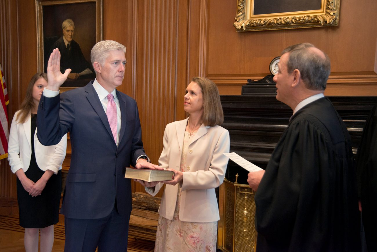 U.S. Chief Justice John Roberts, right, administers the constitutional oath to Judge Neil Gorsuch as his wife, Louise, holds the Bible during an April 10 private ceremony at the Supreme Court in Washington. It was the first of two oaths he was taking to be sworn in as the newest Supreme Court justice. (CNS photo/U.S. Supreme Court via Reuters)