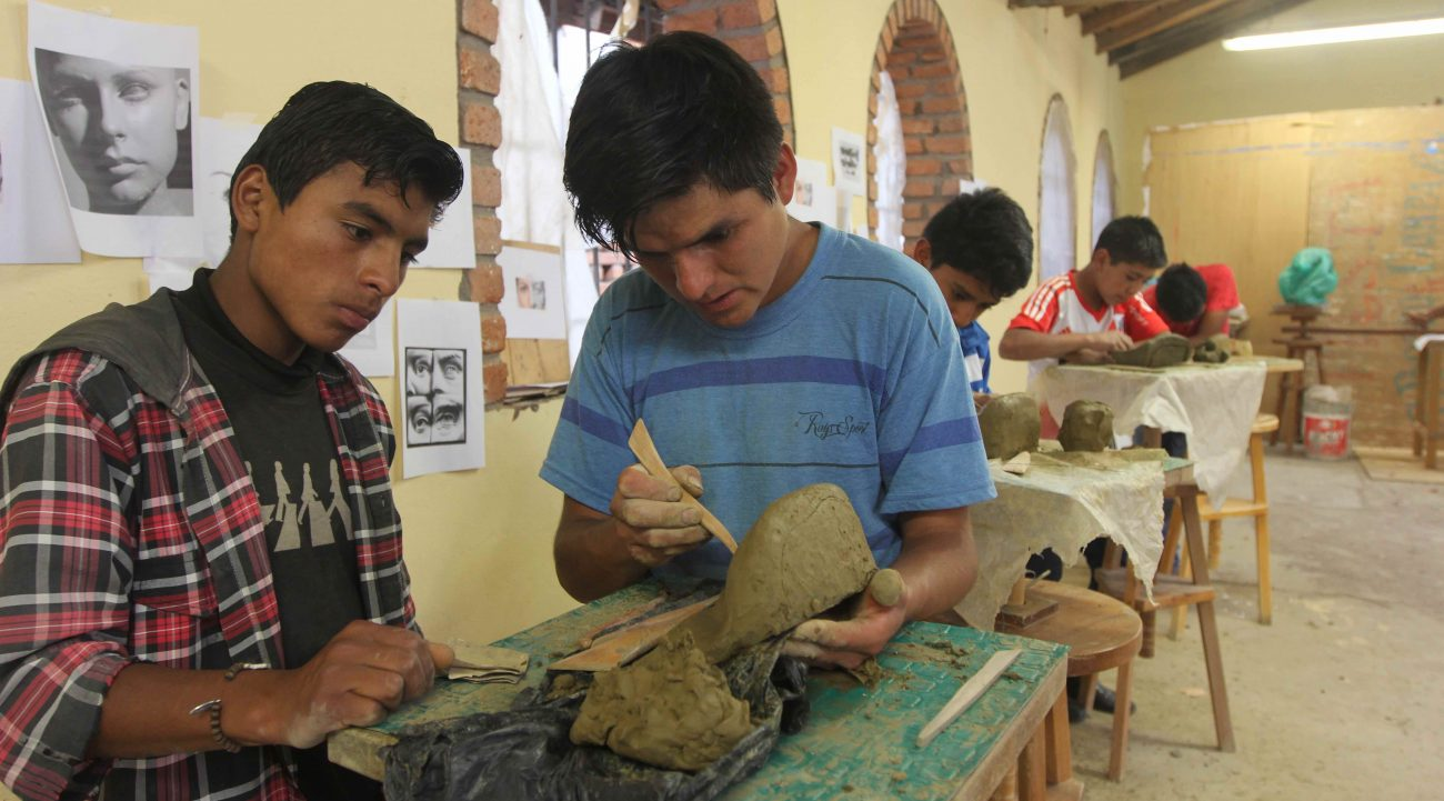 Stonecarver Wagner Lopez, center, gives tips on clay modeling to Omar Palma, 15, during a class April 6 in Jangas, Peru, at the Artesanos Don Bosco boarding school in this Andean town. (CNS photo/Barbara Fraser) See PERU-CARVE-STATUES-NEVADA April 10, 2017