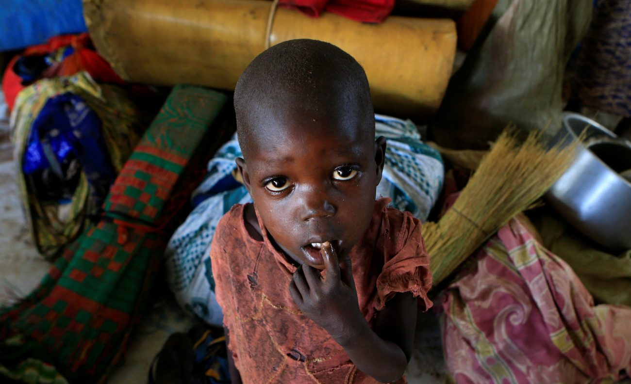 A boy from South Sudan stands next to his family's belongings April 5 at a camp for displaced people in Lamwo, Uganda. As civilians are increasingly targeted in South Sudan's civil war, a bishop urged prominent community leaders speak out. (CNS photo/James Akena, Reuters)