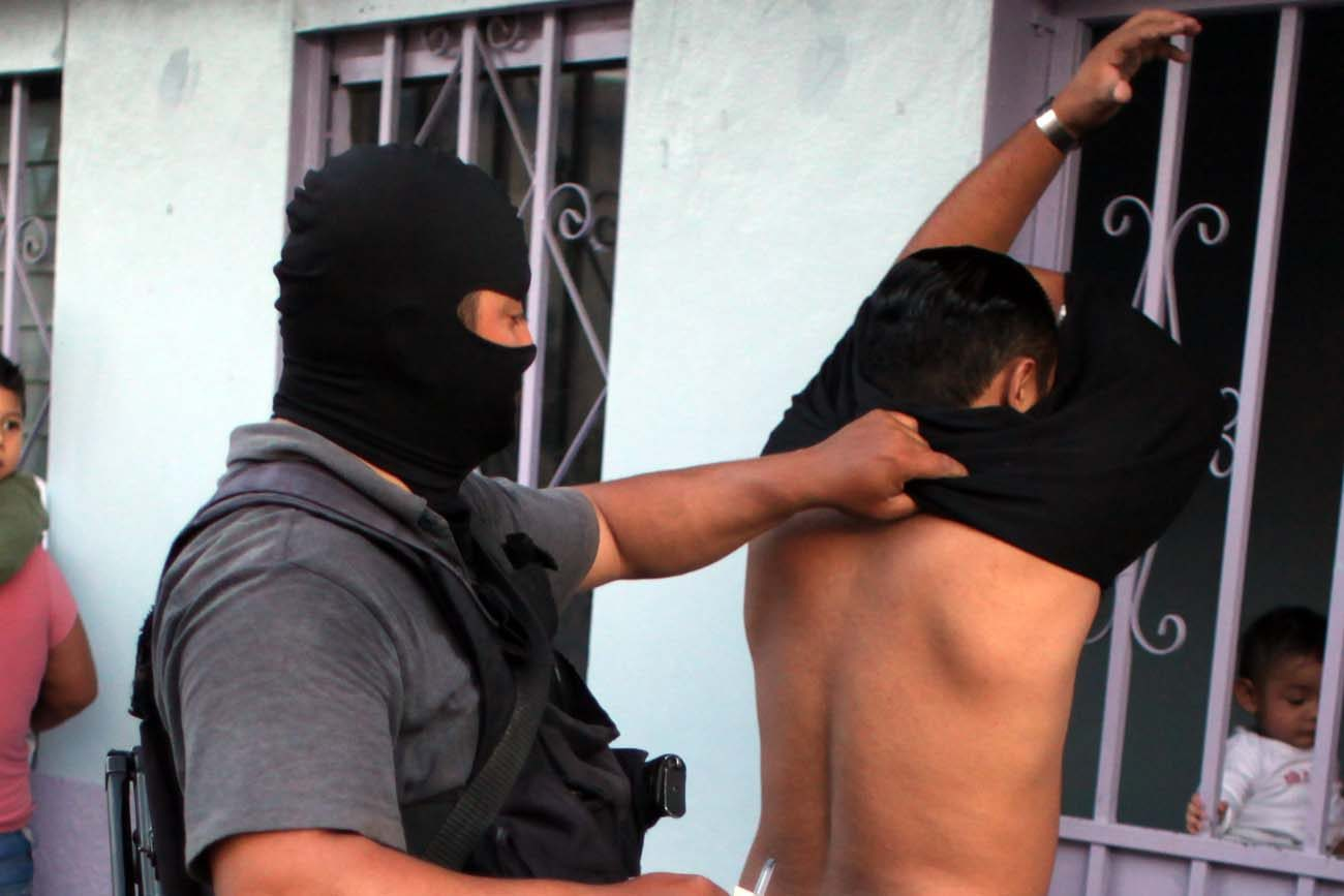 A member of the Honduran police arrests a man during anti-gang operations in 2012 in an area controlled by gang members in Tegucigalpa, Honduras. (CNS photo/Gustavo Amador, EPA)