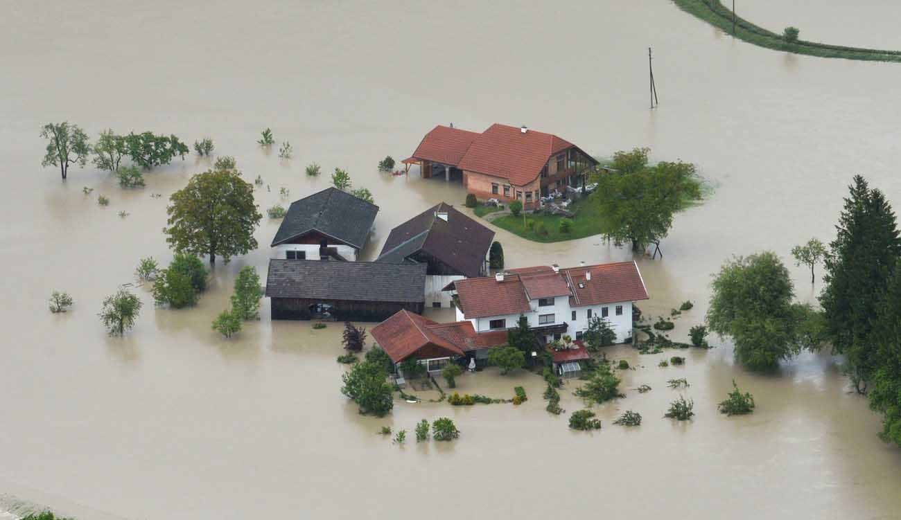 An aerial view shows houses of a farm submerged in floodwater in 2013 near Burghausen, Germany. Catholics participating in the Peoples Climate Movement march April 29 in the nation's capital will be able to pray at a Mass and visit their representatives on Capitol Hill to discuss the issue of climate change. (CNS photo/Peter Kneffel, EPA)