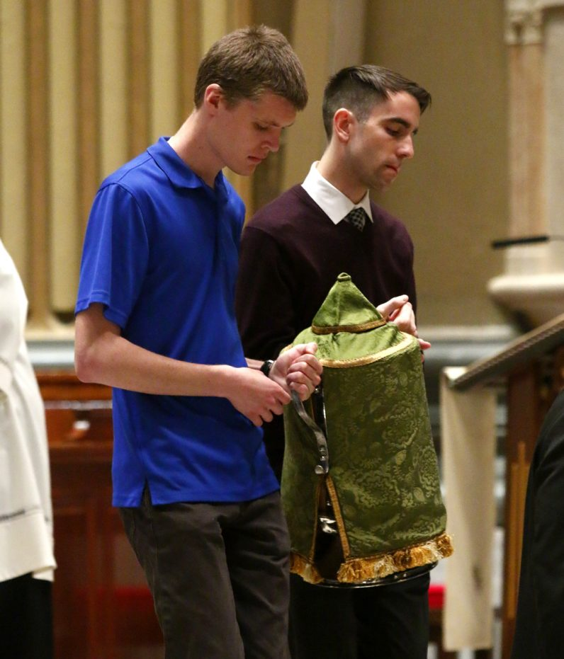 A cask of consecrated oil is brought to the cathedral's chapel where vials of the oils were distributed after Mass to be brought back to the parishes.