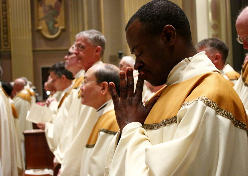 Father Livinus Ugochukwu from St. Cyprian Parish prays during the Holy Thursday Chrism Mass.