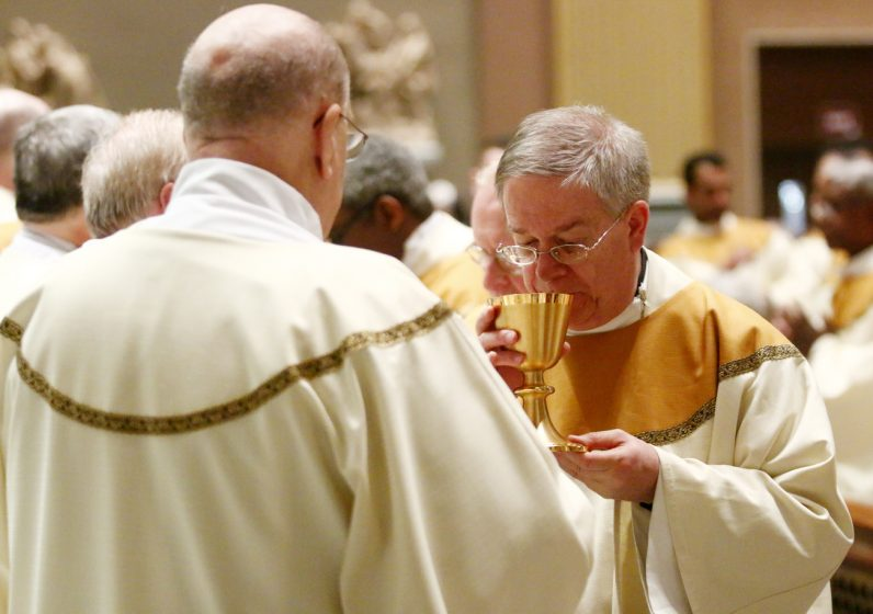 Msgr. Kenneth McAteer drinks the Blood of Christ.