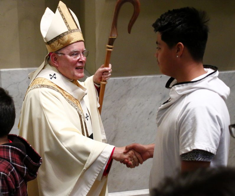 Archbishop Charles Chaput greets a young man from St. Rocco Parish in Avondale after the Chrism Mass.