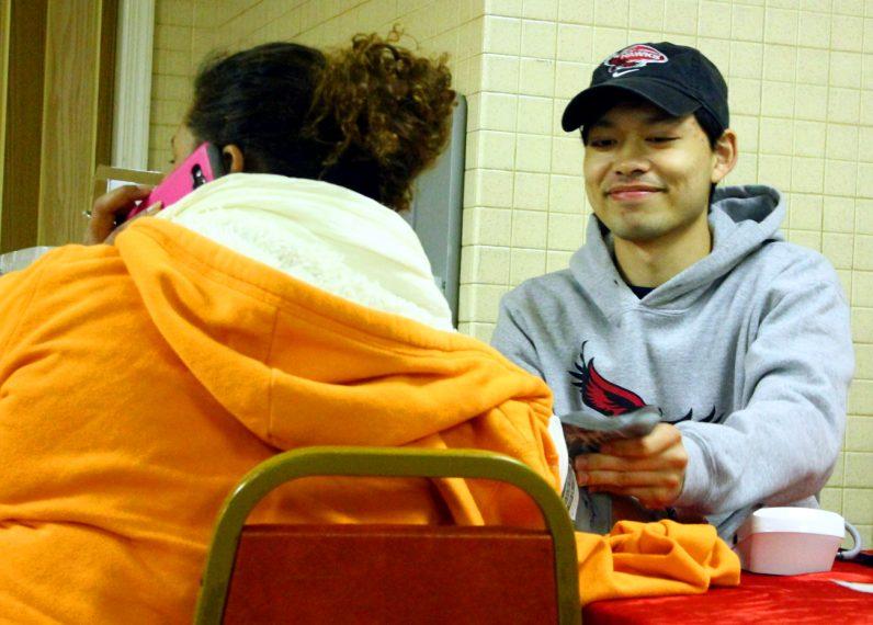 St Joseph University student Gabriel Angeles takes a blood pressure reading.