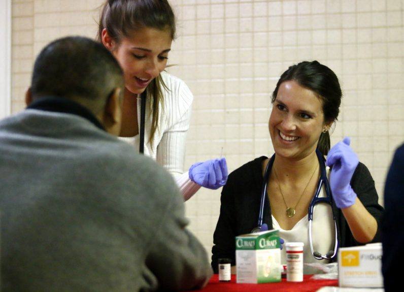 Angelica Italiano (center) and Brighid Imperiale (right), first year  medical students at Philadelphia College of Osteopathic Medicine, perform medical screenings for clients at the monthly health clinic at St. Patrick Church in Norristown. (Sarah Webb)