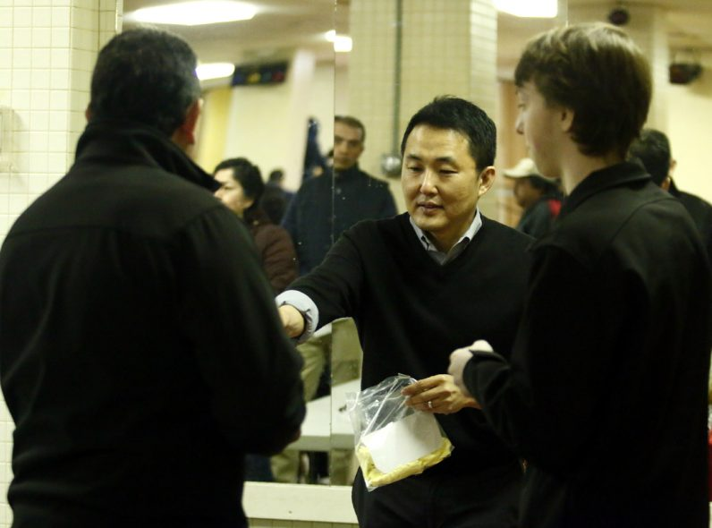 Marvin Lee (center), PdD at the Institute for Bioethics at St Joseph University, and Liam O'Neill (right), fresmand undergrand at St Joseph University, distribute reading glasses to those in need.