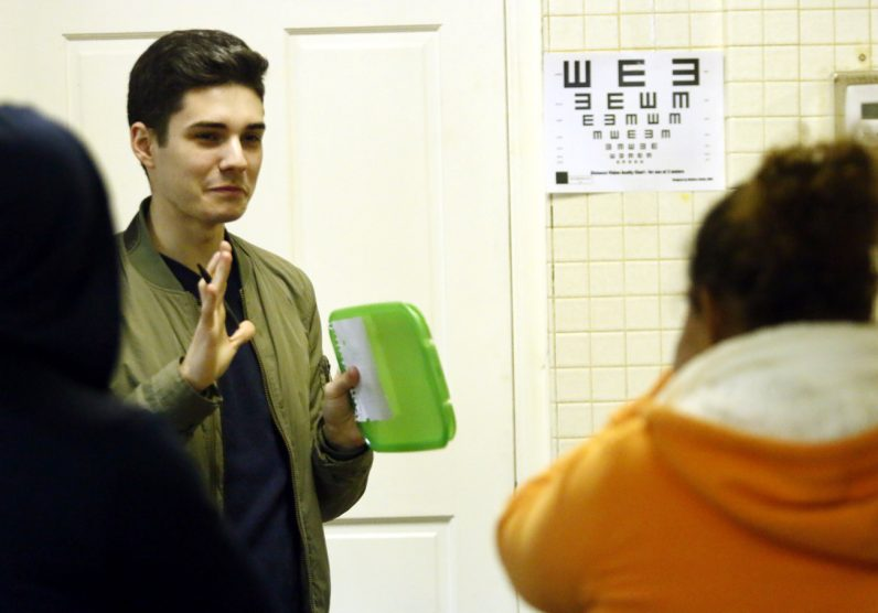 Vincent Pepe, who is bi-lingual, gives and eye exam at the clinic at St Patrick in Norristown.