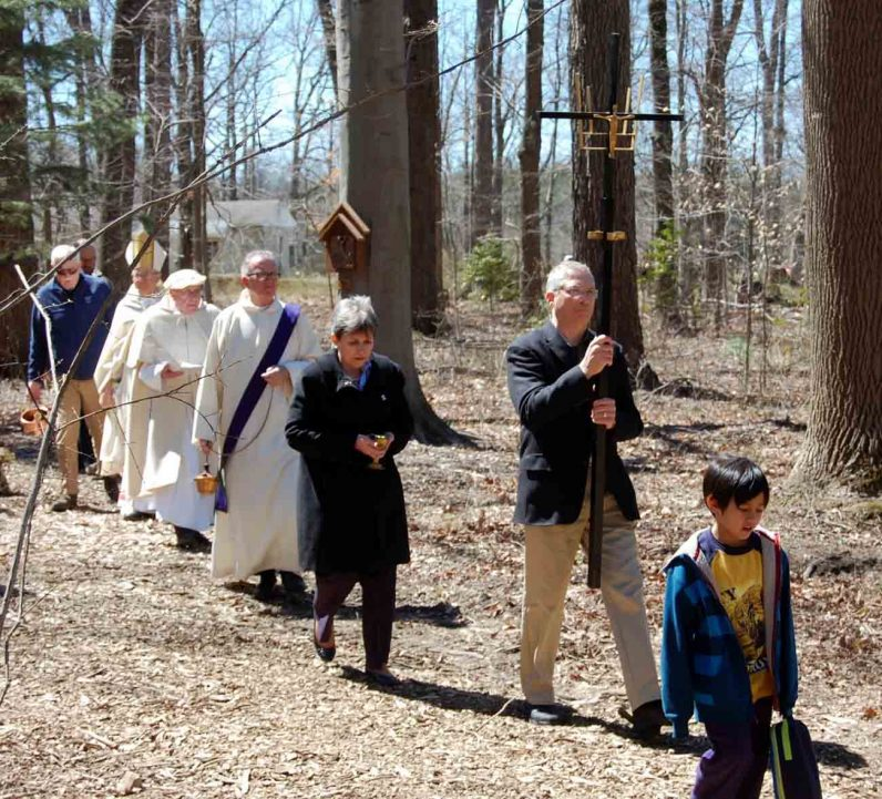 A procession winds along the wooded path of the Stations of the Cross on the Daylesford Abbey grounds during the April 8 blessing ceremony.