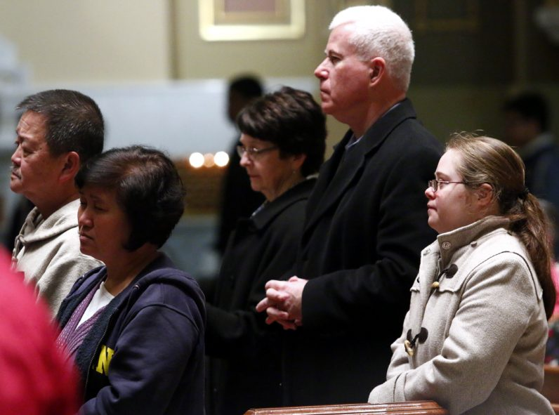 From left, Peg, Mike and Monica Keenan from St. Cyril Parish in Jamison attend Mass as a family.