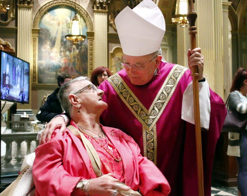 Archbishop Charles Chaput greets Mary Anne Palmer after Mass.