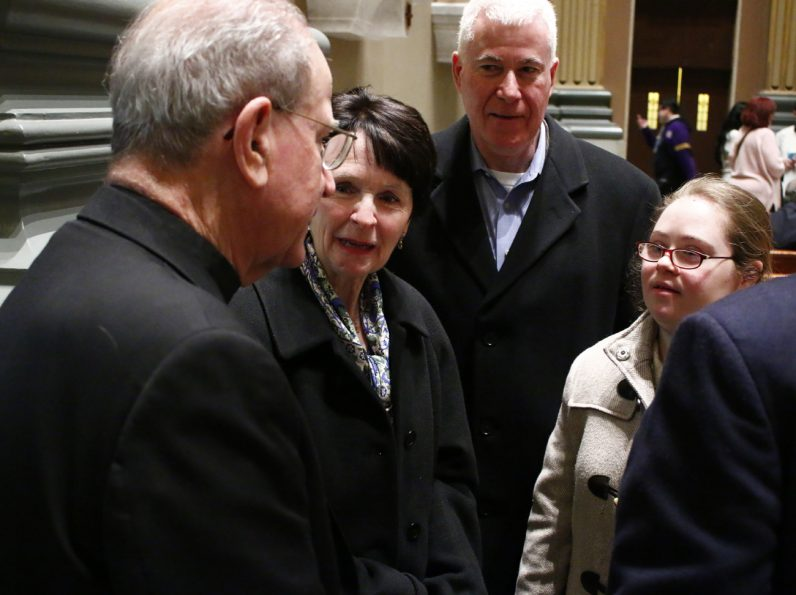 Msgr. Richard Bolger (left) catches up with Peg, Mike and Monica after Mass. Monica attended Our Lady of Confidence School while Msgr. Bolger was pastor of St. David Parish located next to the school.