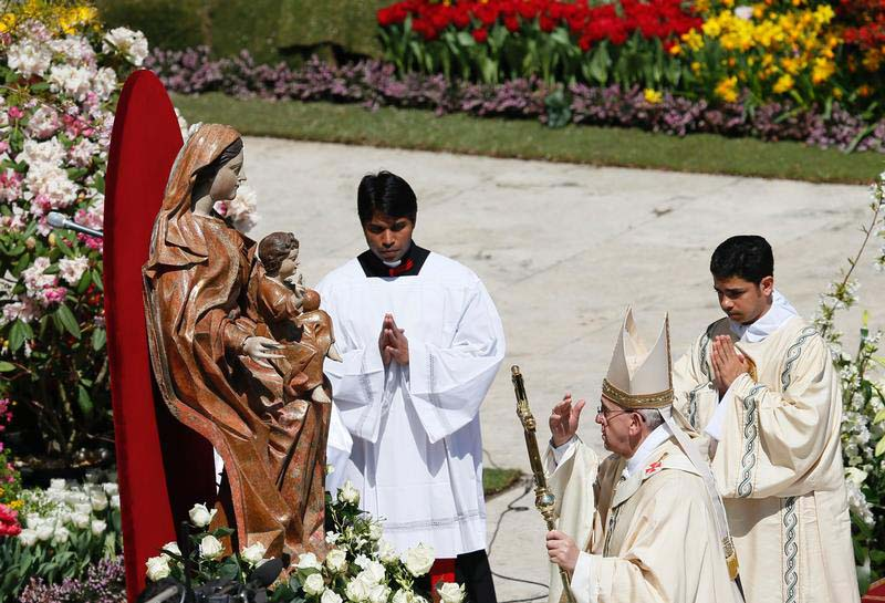 Pope Francis touches a statue of Mary after Easter Mass in St. Peter's Square at the Vatican April 20, 2014. Mary, the mother of Jesus, suffered greatly in the time preceding the resurrection. (CNS photo/Paul Haring)