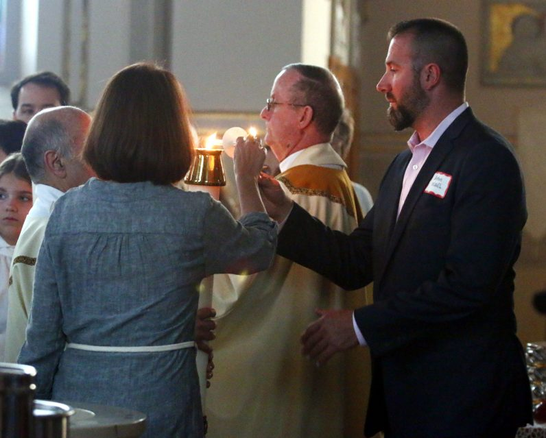 Steve Cassel lights his candle from the paschal candle at the beginning of the Easter Vigil Mass during which he was later  confirmed.