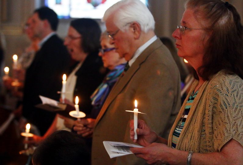Anne Marie McCafferty holds her lit candle at the opening of the Easter Vigil Mass at Sacred Heart  Church in Manoa.
