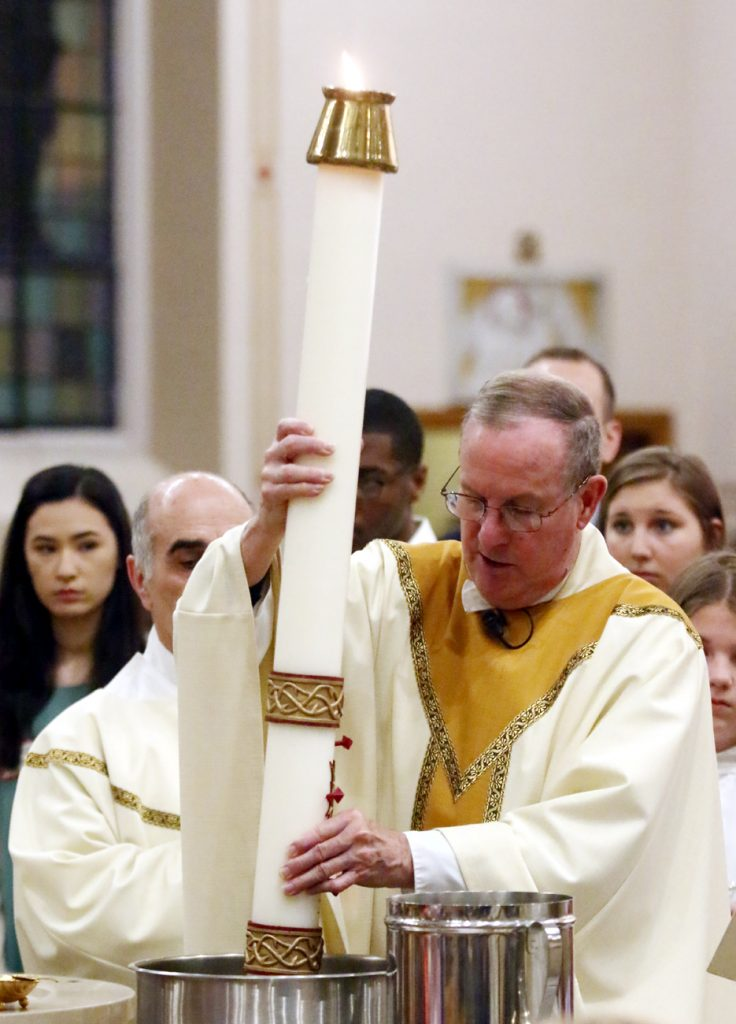 Father Henry McKee, pastor of Sacred Heart Church in Manoa, places the paschal candle in the water for those to be baptized.