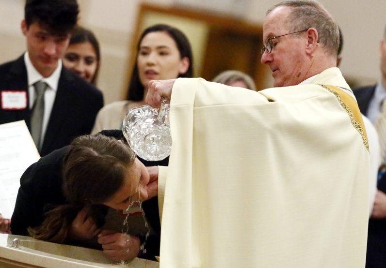 Father Henry McKee, pastor of Sacred Heart Parish in Havertown, baptizes Natalie Coughlin. (Sarah Webb)