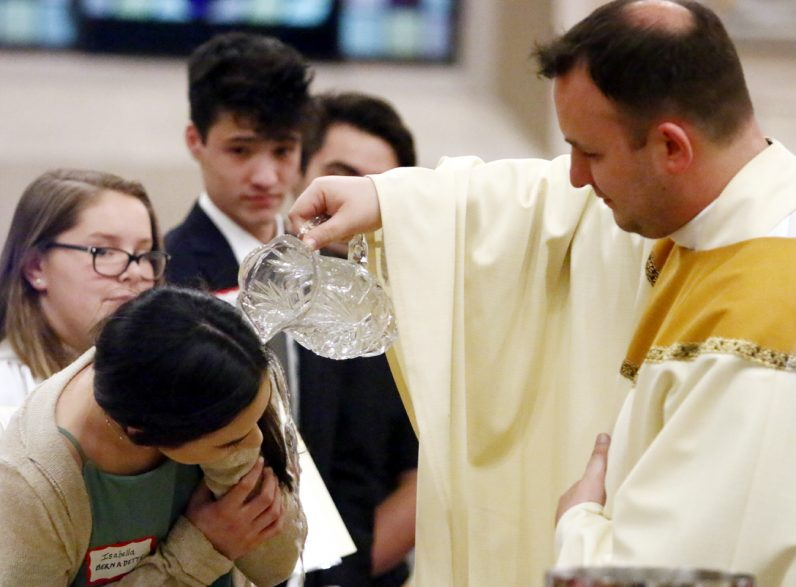 Father Michael Speziale baptizes Isabella Carpenter, from Archbishop Carroll High School, at Sacred Heart Church during the Easter Vigil Mass April 15. (Sarah Webb)
