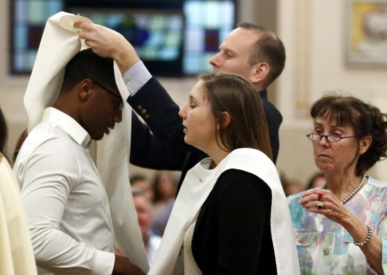 The baptismal sponsors of Christian Smith and Natalie Coughlin place baptismal garments on them as they are received into the Catholic Church. (Sarah Webb)