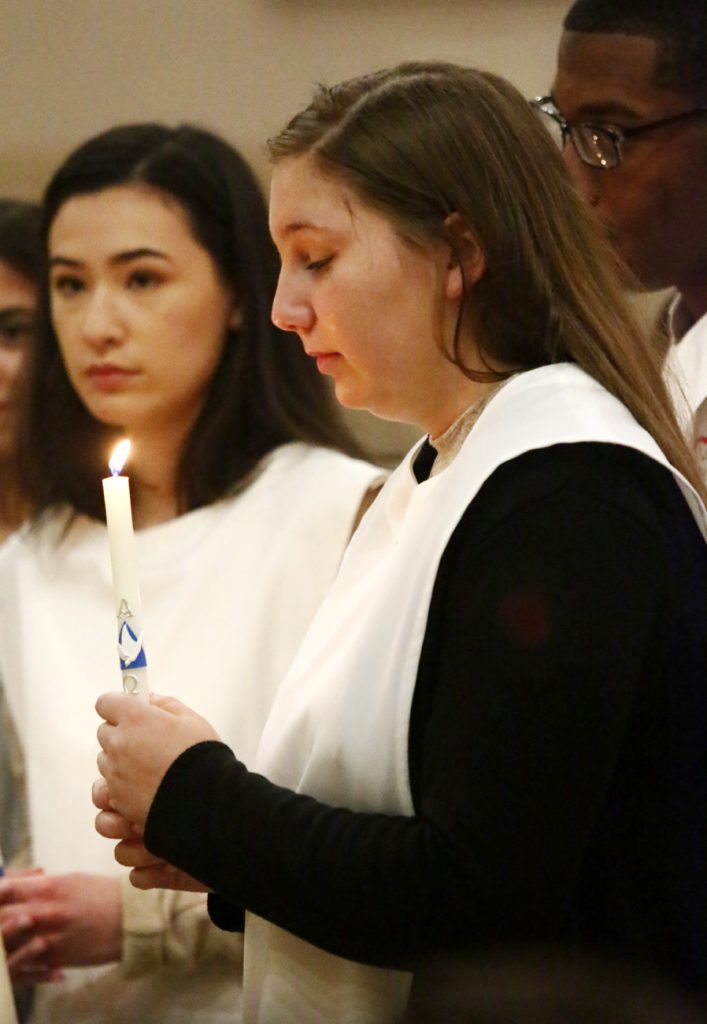 Natalie Coughlin from Sacred Heart Parish looks into the light of her baptismal candle after she enters the church on Saturday, April 15.