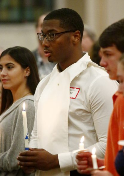 Christian Smith (center) from Archbishop Carroll High School prays during the baptismal rite at Sacred Heart Church during the Easter Vigil Mass. (Sarah Webb)