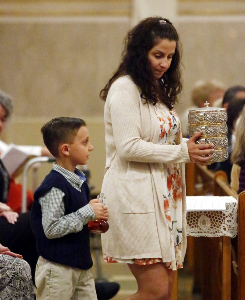 Sammy and his mother Maryanne Sholl bring up the offertory gifts during the Easter Vigil Mass at Sacred Heart Church in Manoa.