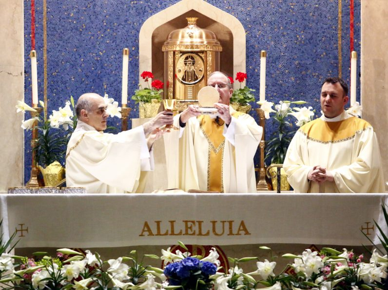 From left, Deacon Bill Williams assists at the altar with Father Henry McKee and Father Michael Speziale.