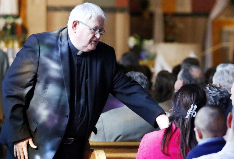 Father Richard Connors, pastor, greets parishioners before Mass at St. David Church in Willow Grove on Easter Sunday.