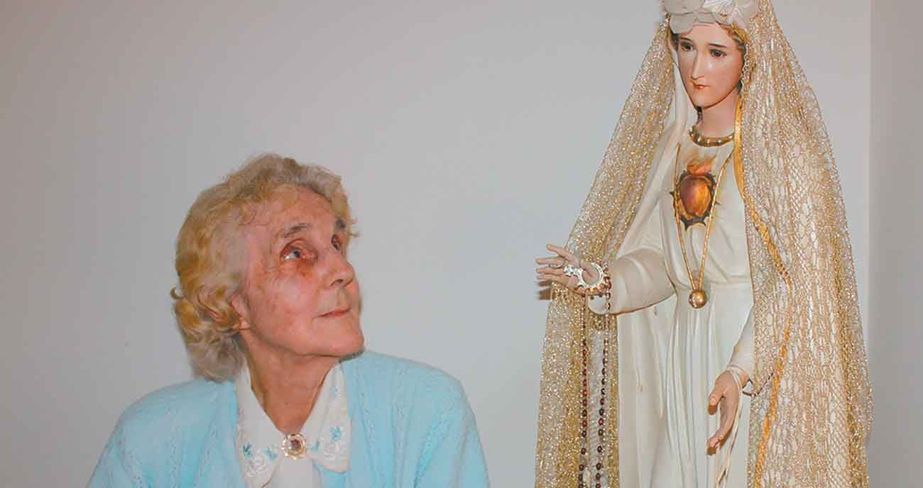 Natalie Martha Loya, pictured in an undated photo, gazes at a statue of Our Lady of Fatima that crisscrossed the country with her during her 35-year apostolate of spreading the Fatima message. Loya, a Byzantine Catholic who lives in the Eparchy of Parma, Ohio, received the statue from her father, the late Father John Loya, who purchased it for her at a gift shop in Fatima, Portugal. (CNS photo/Laura Leraci, Horizons Newspaper)