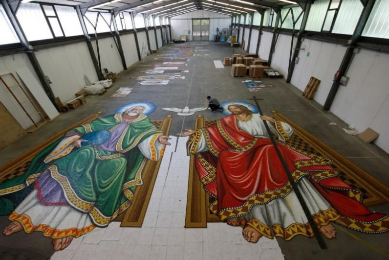 A man works on a section of a mosaic with figures of God the Father and Jesus in 2016 in the warehouse of the Travisanutto Giovanni mosaic company in Spilimbergo, Italy. Creating art can put an artist in touch with the religious sense that has been worked into the very life of the land. (CNS photo/Paul Haring).
