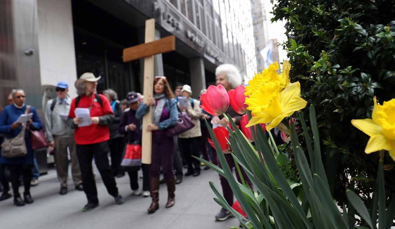 """Participants process through the streets of midtown Manhattan during the 35th annual Pax Christi Metro New York Way of the Cross/Way of Peace April 14 in New York City. """"Jesus Calls Us to Active Nonviolence"""" was the theme of this year's Good Friday commemoration. (CNS photo/Gregory A. Shemitz)"""