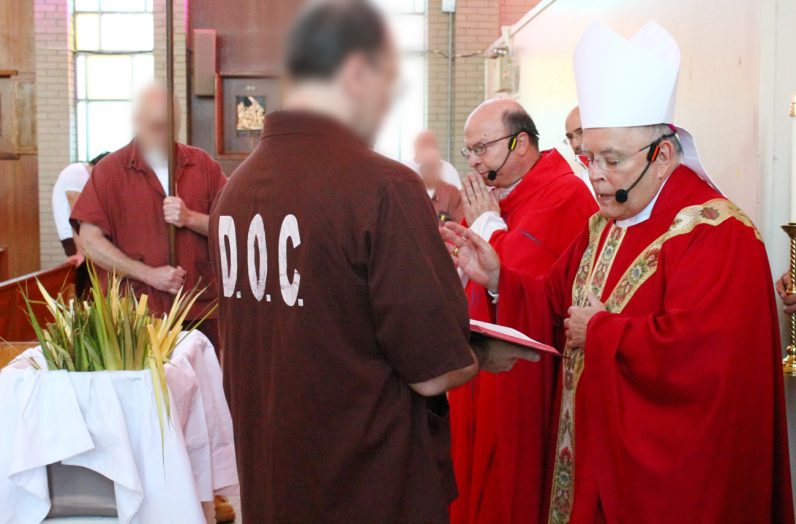 Archbishop Charles Chaput blesses palm during his visit to SCI Graterford on April 8.