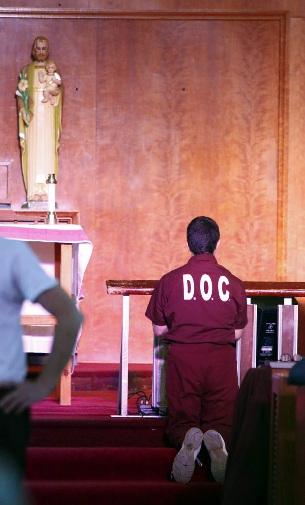 An inmate prays before Mass at SCI Graterford.