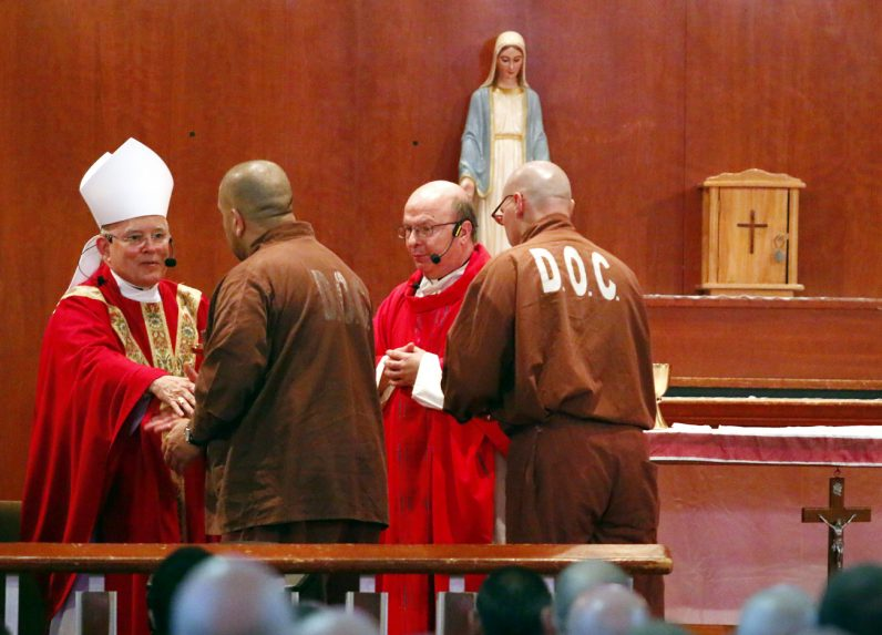 Two inmates present the offertory gifts to Archbishop Charles Chaput during Mass at SCI Graterford.