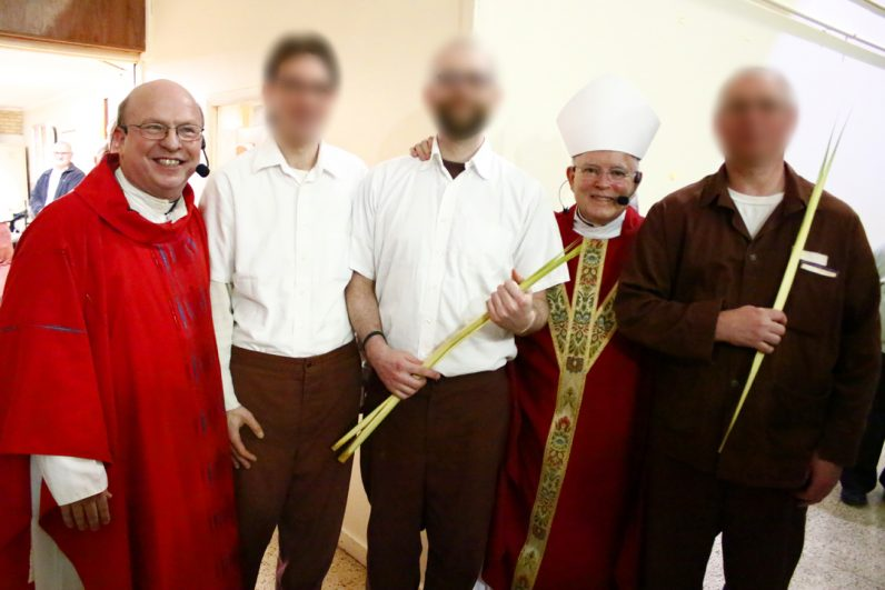 Father John Pidgeon, chaplain at SCI Graterford, and Archbishop Charles Chaput pose for a picture with three gentlemen who will be baptized and received into the Catholic Church at the Easter Vigil Mass in the prison.