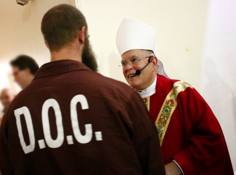 After celebrating Palm Sunday Mass April 8 at Graterford Prison in Schwenksville, Archbishop Charles Chaput chats with and offers a blessing to a young man who was to be released from the state prison the next day. (Sarah Webb)