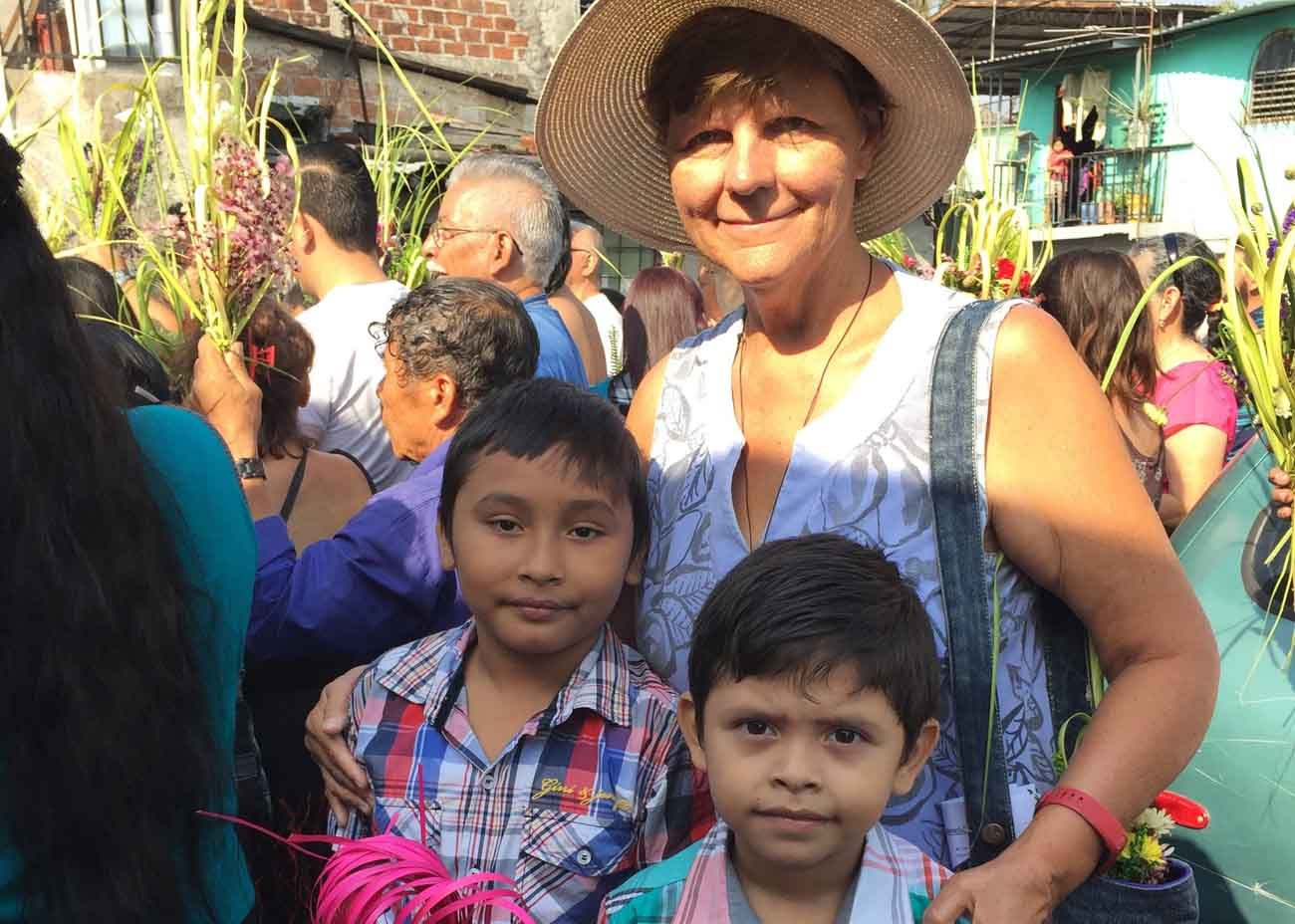 Margie Legowski, a member of Holy Trinity Catholic Church in Washington's, poses for a Palm Sunday photo April 9 with children from Holy Trinity's sister parish, Maria Madre de los Pobres Church in San Salvador, El Salvador. The sister parish is in one of the most dangerous zones of San Salvador, but it also offers great spiritual lessons of hope and love during Holy Week, says Legowski. (CNS photo/courtesy Margie Legowski)