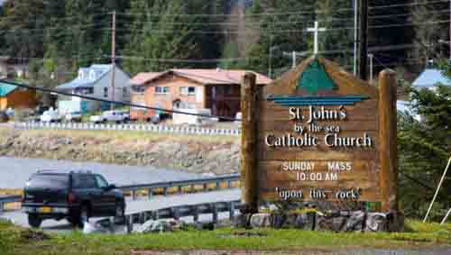 A vehicle drives past a sign for St. John by the Sea Church off the main road leading to Klawock and Craig on Prince of Wales Island in southeastern Alaska. The island is accessible only by boat, ferry or seaplane. (CNS photo/Nancy Wiechec)