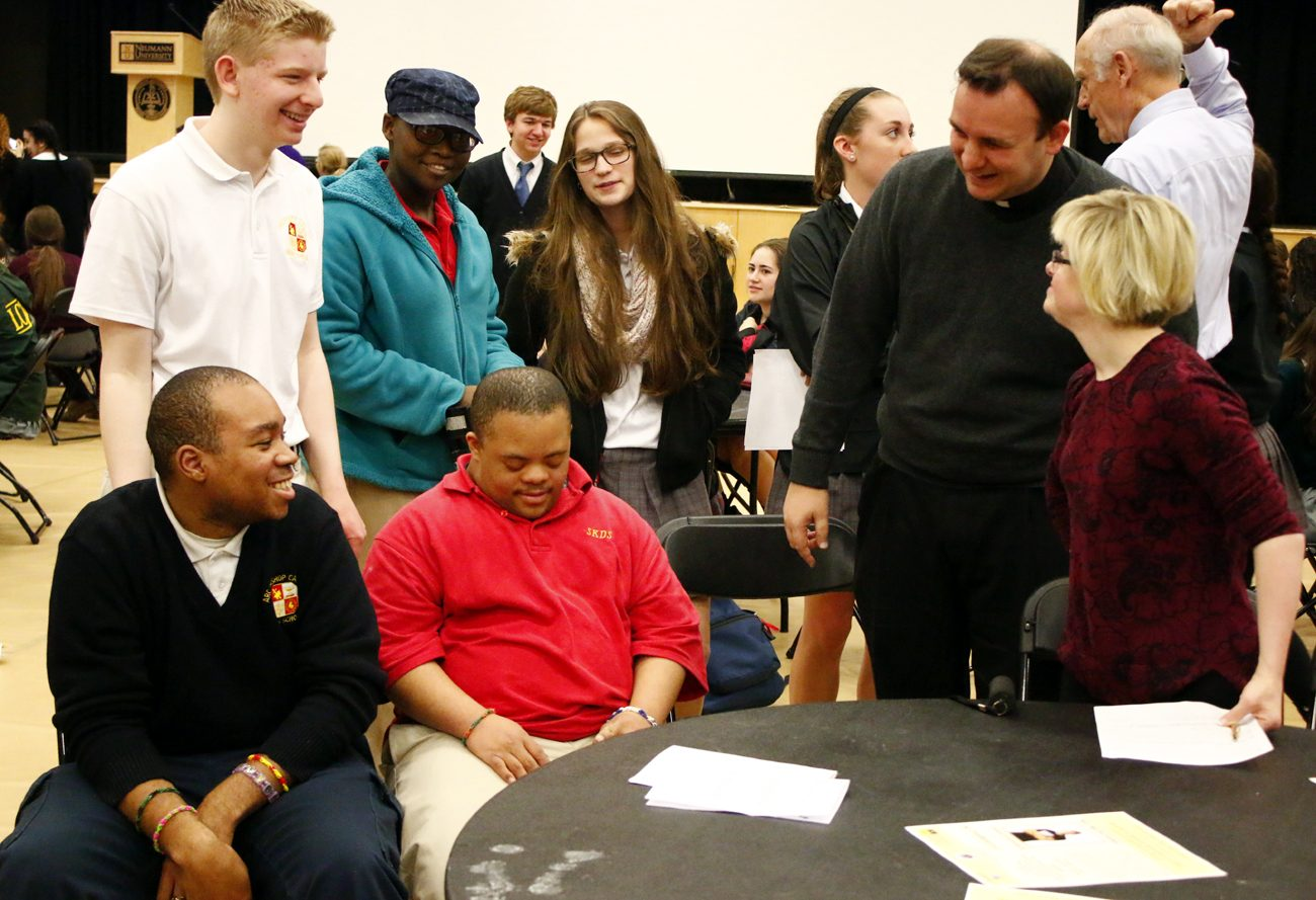Dr. Karen Gaffney, right, chats with Archbishop Carroll High School's chaplain, Father Michael Speziale, and students from Carroll and their buddies at  St. Kathrine Day School. (Sarah Webb)